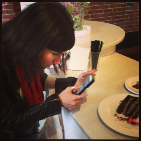 Author Terry Hope Romero photographing the Chocolate Caramel Pistachio Torte at Petunia's Pies & Pastries.